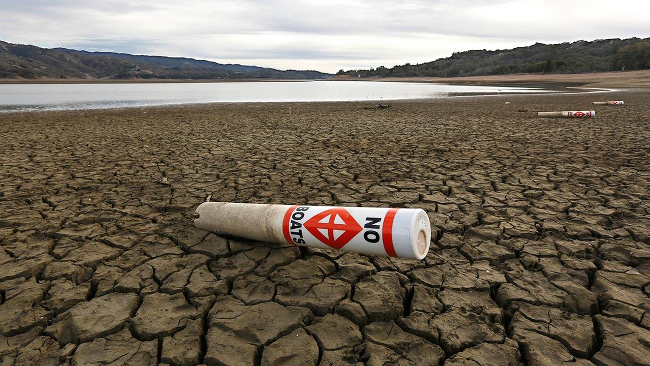 FILE - In this Feb. 4 2014 file photo, a warning buoy sits on the dry, cracked bed of Lake Mendocino near Ukiah, Calif.