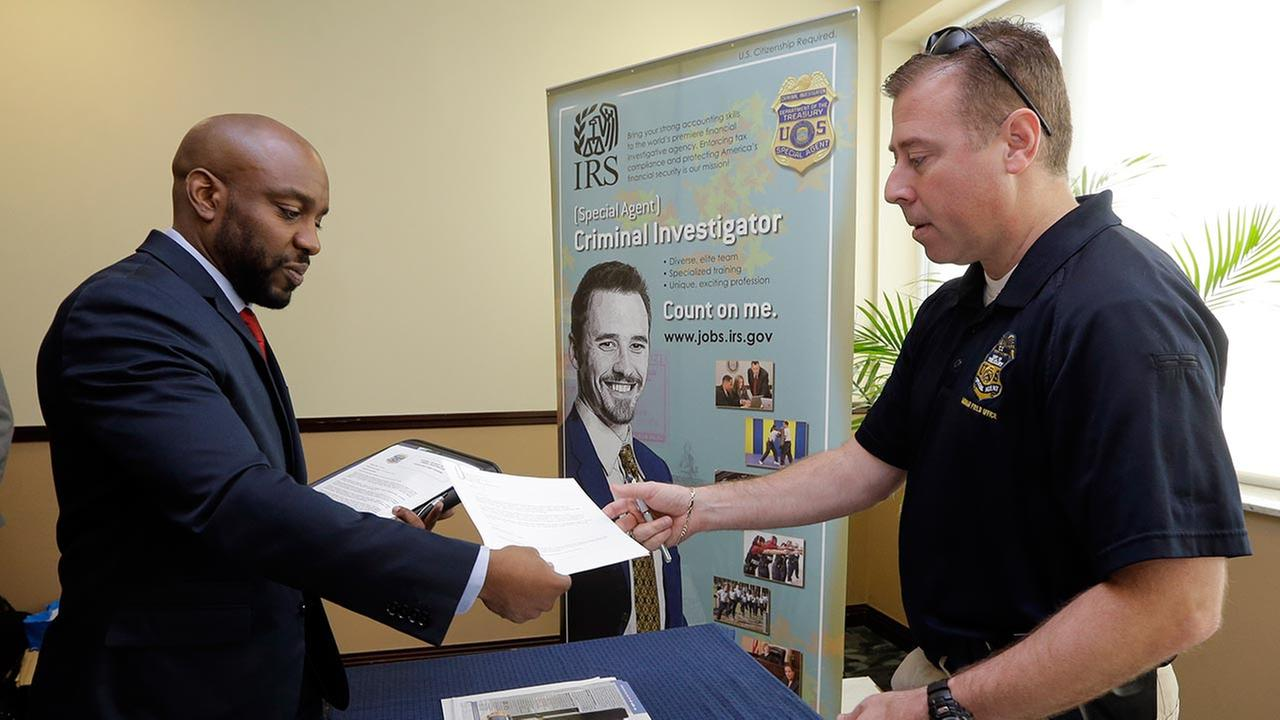 U.S. Marine Corps Veteran Arlington Robertson, of Fort Lauderdale, left, hands his resume to an Internal Revenue Service Special Agent, at the annual Veterans Career and Resource Fair in Miami