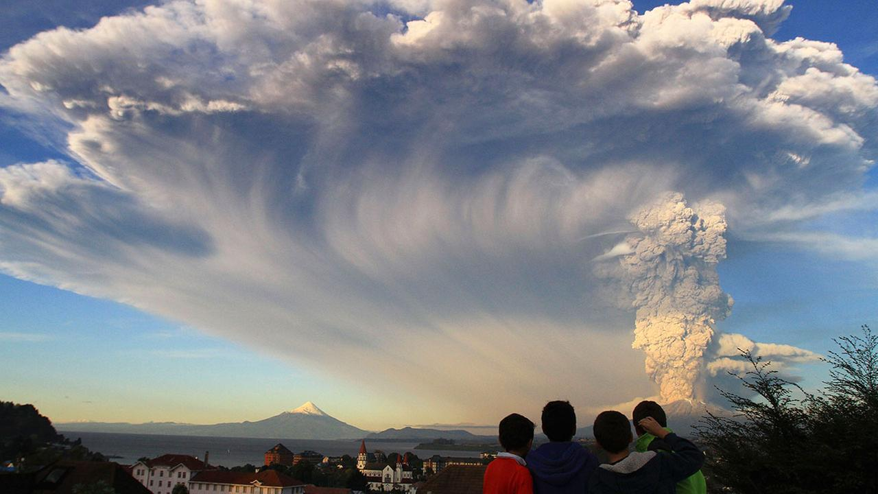 Children watch the Calbuco volcano erupt, from Puerto Varas, Chile, Wednesday, April 22, 2015.
