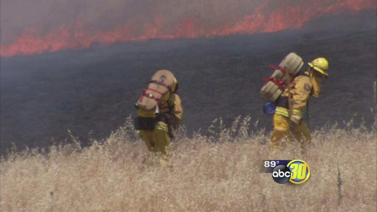 Firefighters battling wildfires and for higher pay