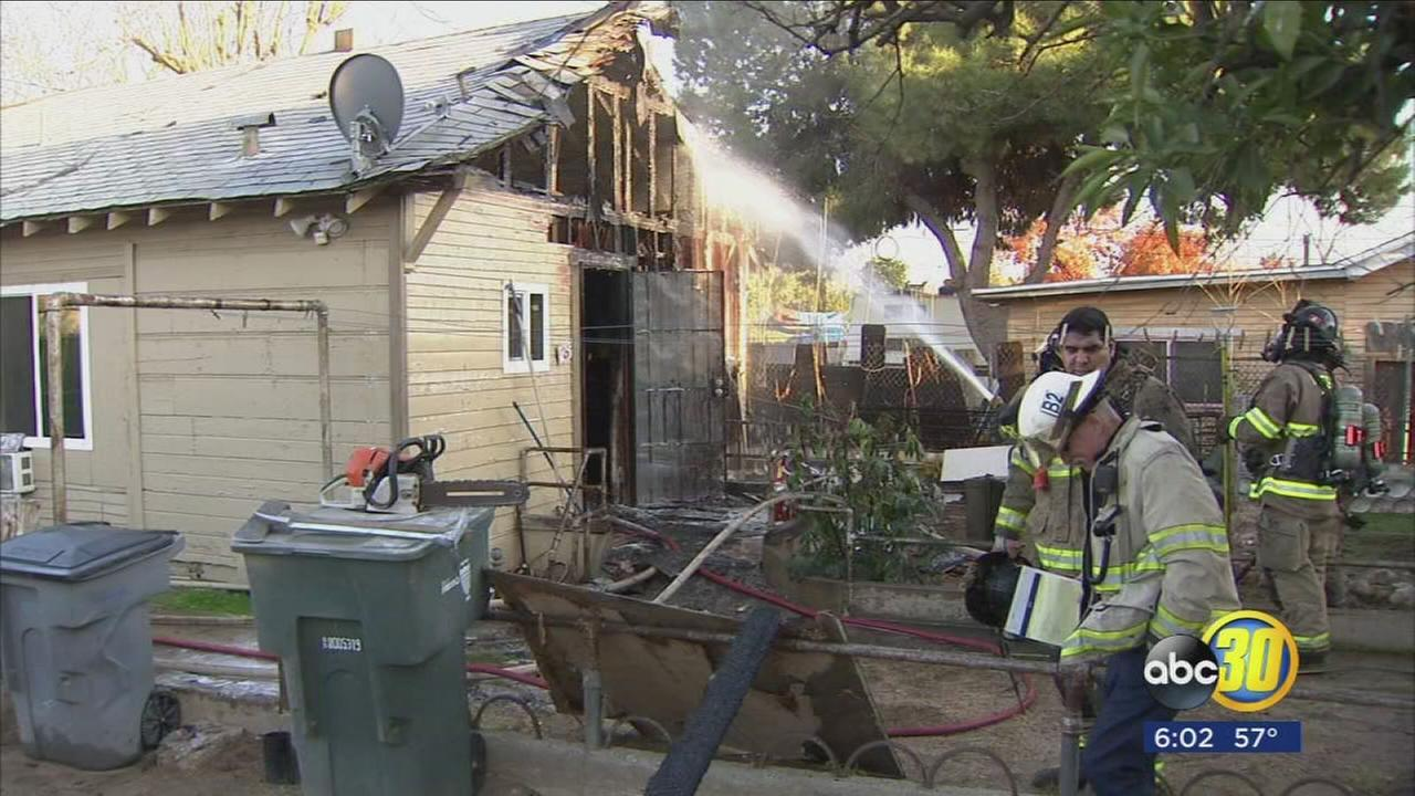Woman hospitalized after building catches fire in Southwest Fresno