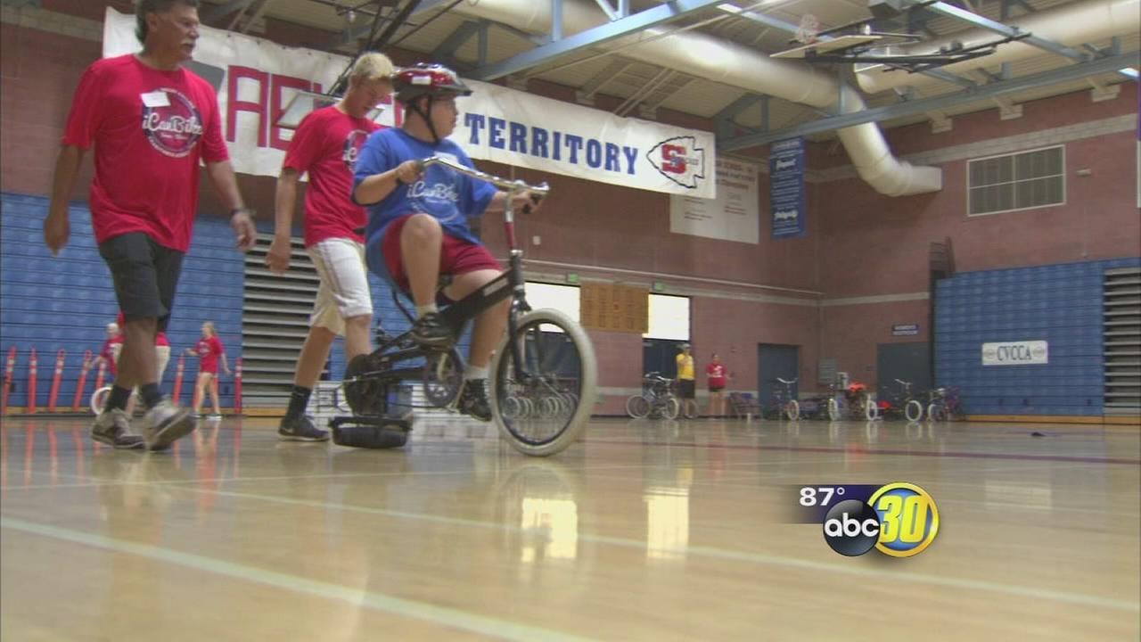 Children with disabilities learn how to ride bikes in Sanger