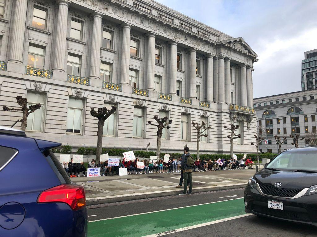 <div class='meta'><div class='origin-logo' data-origin='none'></div><span class='caption-text' data-credit='@phoenixspirit/Twitter'>People are seen holding signs in front of city hall in San Francisco, Calif. on Wednesday, March <br>14, 2018 during a walkout in response to gun violence.</span></div>