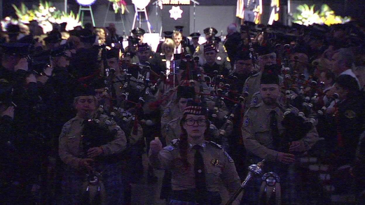<div class='meta'><div class='origin-logo' data-origin='none'></div><span class='caption-text' data-credit=''>Bagpipe players lead the casket of Officer Michael Johnson out of the SAP Center after his memorial service on Thursday, April 2, 2105. (KGO-TV)</span></div>