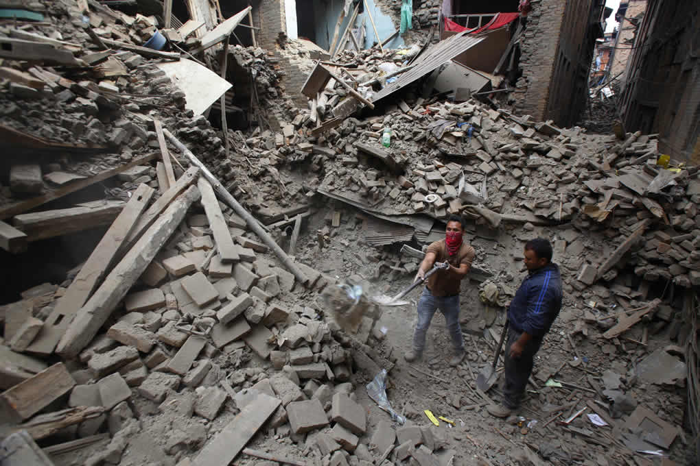 Rescue workers remove debris as they search for victims of earthquake ...