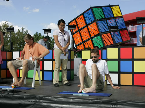 Oliver Wolff, right, of Germany, sets a new world record by solving a Rubik's Cube with his feet in one minute, 54 seconds.(AP Photo/Walt Disney world, Todd Anderson)