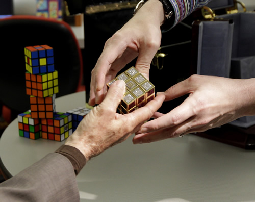 Erno Rubik, left, the inventor of the Rubik's Cube, reaches out to receive a gold and gemstone version of his cube worth $2.5M. (AP Photo/Julio Cortez)