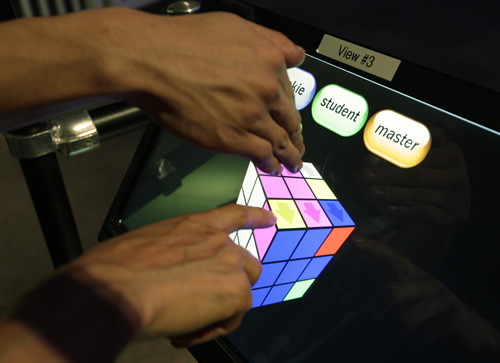 "A visitor uses a touch-screen computer to work on solving the ""Groovik's Cube,"" a 35-foot fully playable illuminated sculpture based on the Rubik's Cube. (AP Photo/Ted S. Warren)"