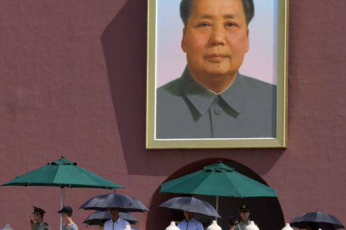 Uniformed and plainclothes security personnel with umbrellas are on duty near a portrait of late Chinese leader Mao Zedong in Beijing Tuesday, June 3, 2014. (AP Photo/Ng Han Guan)
