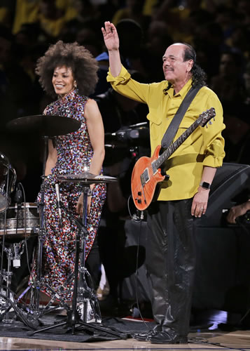 <div class='meta'><div class='origin-logo' data-origin='none'></div><span class='caption-text' data-credit='AP Photo/Ben Margot'>Carlos Santana, right, waves after he and his wife Cindy Blackman Santana performed the national anthem before Game 2 of basketball's NBA Finals.</span></div>