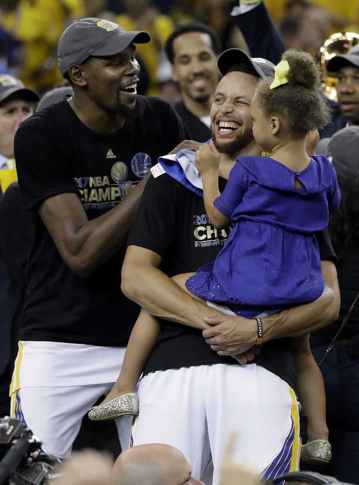 <div class='meta'><div class='origin-logo' data-origin='none'></div><span class='caption-text' data-credit='AP Photo/Marcio Jose Sanchez'>Warriors guard Stephen Curry, center, holds his daughter Riley as they celebrate with forward Kevin Durant, left, after the NBA Finals in Oakland, Calif. on June 12, 2017.</span></div>