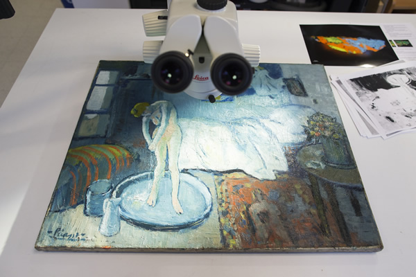"""The Blue Room,"" one of Pablo Picasso's first masterpieces sits under a microscope at The Phillips Collection, on Tuesday, June 10, 2014, in Washington. (AP Photo/ Evan Vucci)"
