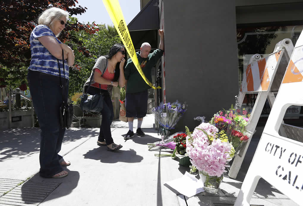<div class='meta'><div class='origin-logo' data-origin='none'></div><span class='caption-text' data-credit='AP Photo/Jeff Chiu'>Two women and a man look at a makeshift memorial for victims of a balcony that collapsed in Berkeley, Calif., Tuesday, June 16, 2015.</span></div>