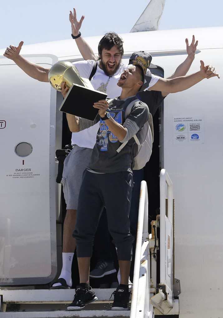 <div class='meta'><div class='origin-logo' data-origin='none'></div><span class='caption-text' data-credit='AP Photo/Jeff Chiu'>Warriors guard Stephen Curry yells as he carries the NBA championship trophy in front of center Andrew Bogut after the team's flight landed in Oakland, Calif., June 17, 2015.</span></div>