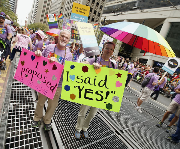 <div class='meta'><div class='origin-logo' data-origin='none'></div><span class='caption-text' data-credit='AP Photo/ Tony Avelar'>Ruel Walker, left, and Bertron Vandeville, hold up signs as they marched in the 45th annual San Francisco Gay Pride parade Sunday, June 28, 2015, in San Francisco.</span></div>