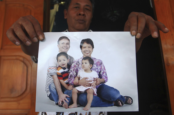 Indonesian resident Widi Yuwono, the brother of Yuli Hastini, rear, holds a photograph of his sister's family who were on Malaysia Airlines Flight 17. (AP Photo) <span class=meta></span>