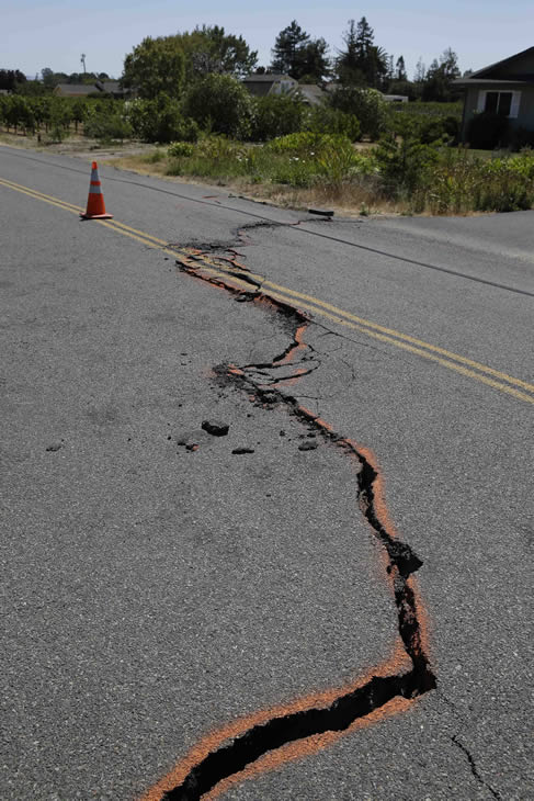 A cracked section of roadway is shown in the Carneros district following an earthquake Sunday, Aug. 24, 2014, in Napa, Calif. (AP Photo/Eric Risberg) <span class=meta></span>