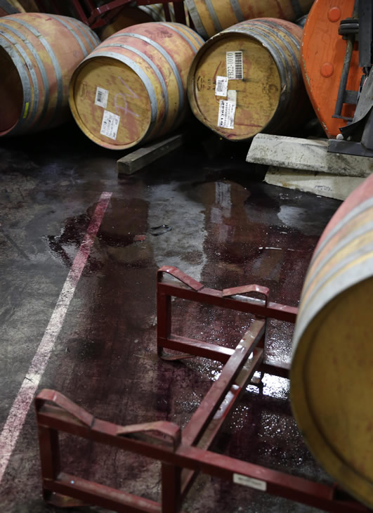 Wine leaks from some of the hundreds of earthquake damaged wine barrels at the Kieu Hoang Winery Monday, Aug. 25, 2014, in Napa, Calif.  (AP Photo/Eric Risberg)