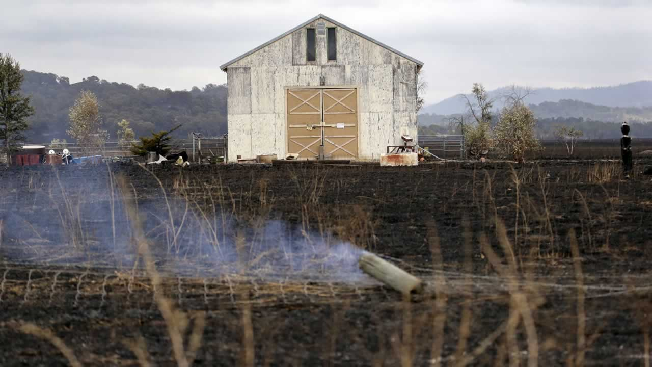 <div class='meta'><div class='origin-logo' data-origin='none'></div><span class='caption-text' data-credit='AP Photo/Elaine Thompson'>A barn stands undamaged while surrounded by blackened grasses and in view of still smoldering fence posts Monday, Sept. 14, 2015, near Middletown, Calif.</span></div>