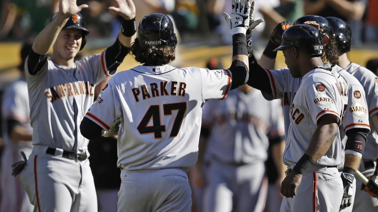 San Francisco Giants Jarrett Parker (47) is congratulated by teammates after hitting a grand slam off Oakland Athletics Ryan Dull in the eighth inning of a baseball game Saturday, Sept. 26, 2015, in Oakland, Calif.