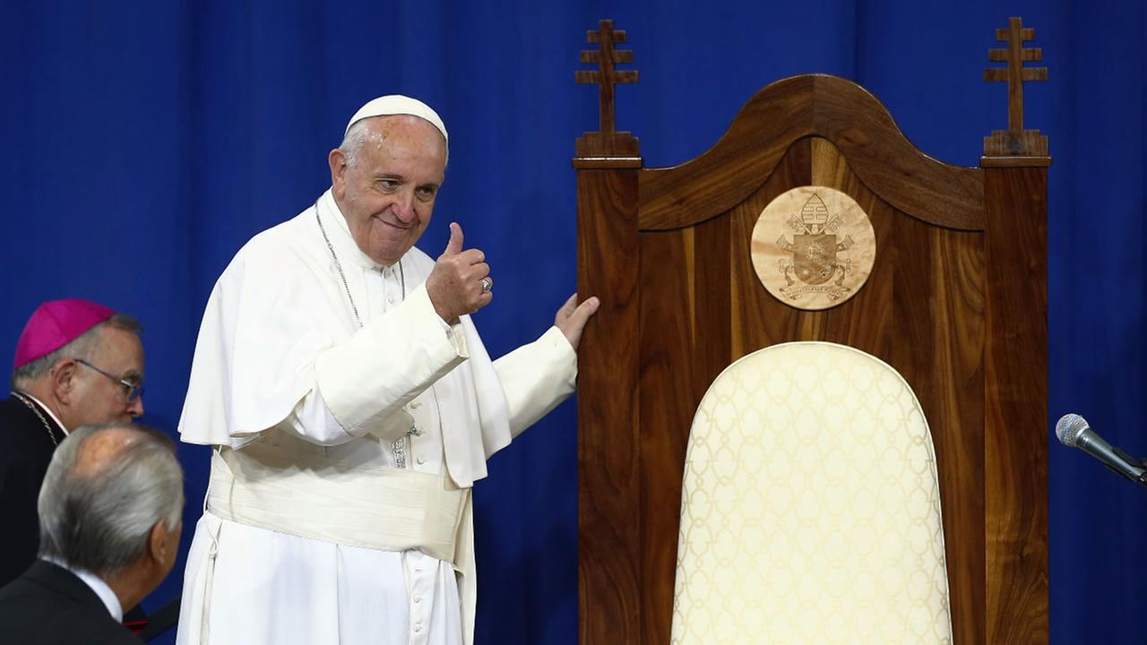 Pope Francis gestures to inmates next to a wooden chair made for him by inmates during his visit to Curran-Fromhold Correctional Facility in Philadelphia, Sunday, Sept. 27, 2015.