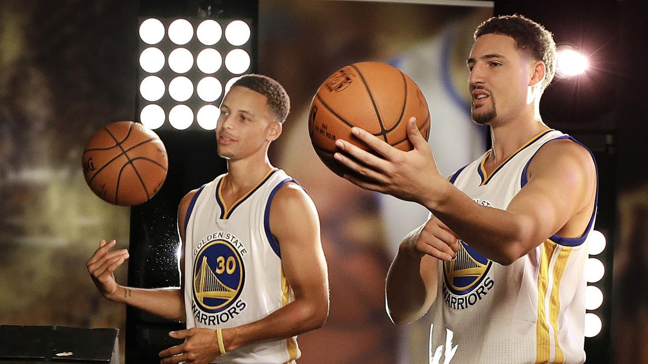 Golden State Warriors Stephen Curry, left, and Klay Thompson (11) pose for photographs during an NBA basketball media day Monday, Sept. 28, 2015, in Oakland, Calif.
