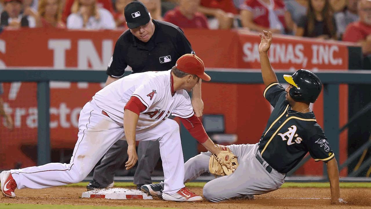 Oakland Athletics Marcus Semien, right, is tagged out at third by Los Angeles Angels third baseman David Freese Monday, Sept. 28, 2015, in Anaheim, Calif.