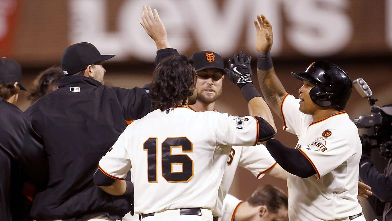 San Francisco Giants Marlon Byrd celebrates with teammates after scoring the winning run on a sacrifice fly ball by Alejandro De Aza against the LA Dodgers Monday, Sept. 28, 2015.