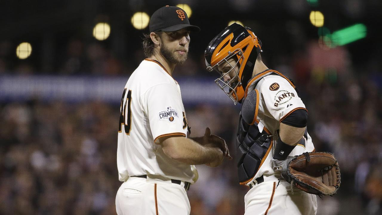 San Francisco Giants pitcher Madison Bumgarner, meets with catcher Buster Posey during the fifth inning of a game against the Los Angeles Dodgers in San Francisco, Sept. 29, 2015.