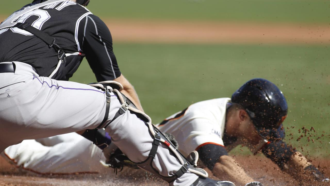 San Francisco Giants Kelby Tomlinson dives safely into home for an inside-the-park home run during the first inning of a baseball game, Saturday, Oct. 3, 2015, in San Francisco.