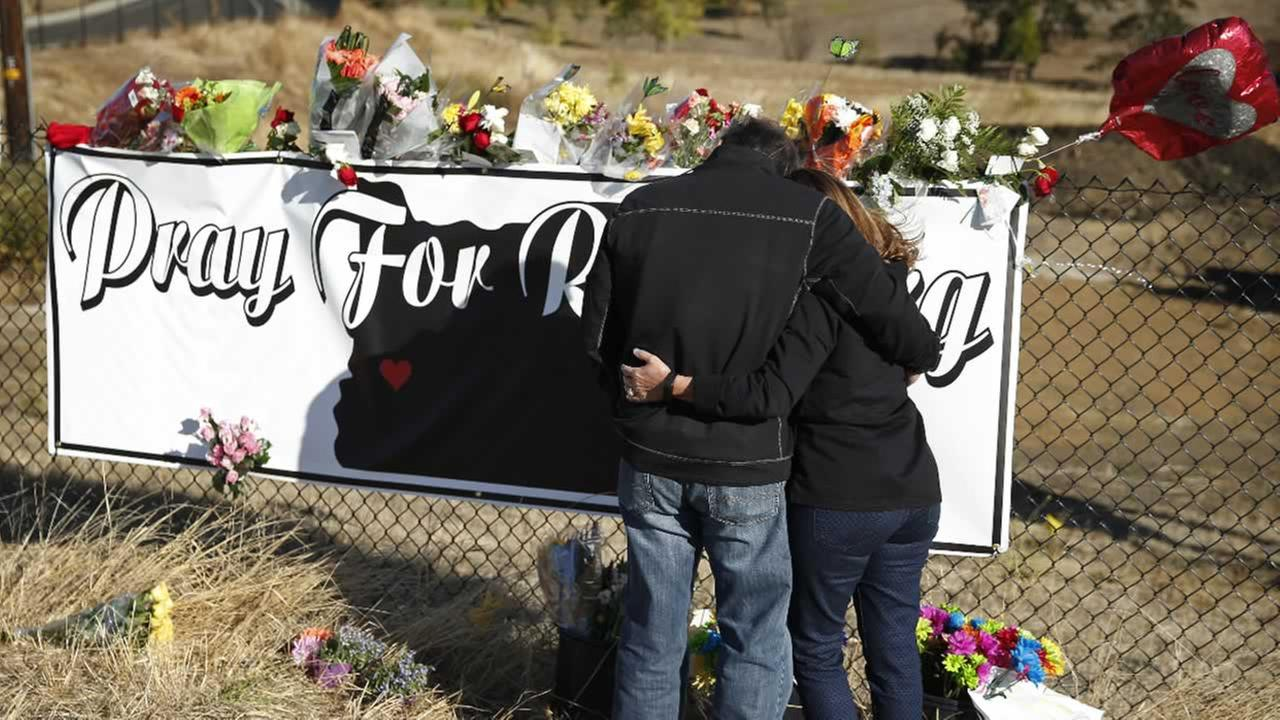 Charley Thompson and his wife Rachel Thompson embrace as they place flowers at a makeshift memorial near the road leading to Umpqua Community College, Saturday, Oct. 3, 2015.