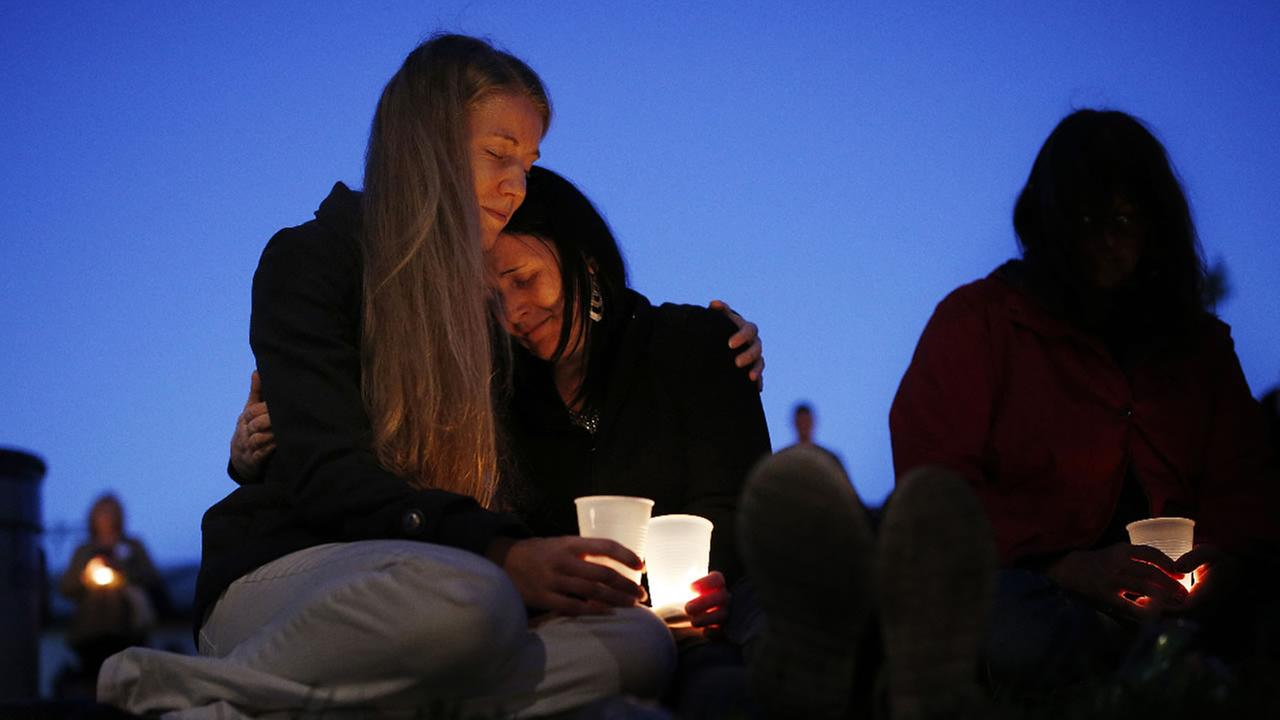 Heidi Wickersham, left, embraces her sister Gwendoline Wickersham during a prayer vigil Saturday, Oct. 3, 2015, in Winston, Ore.