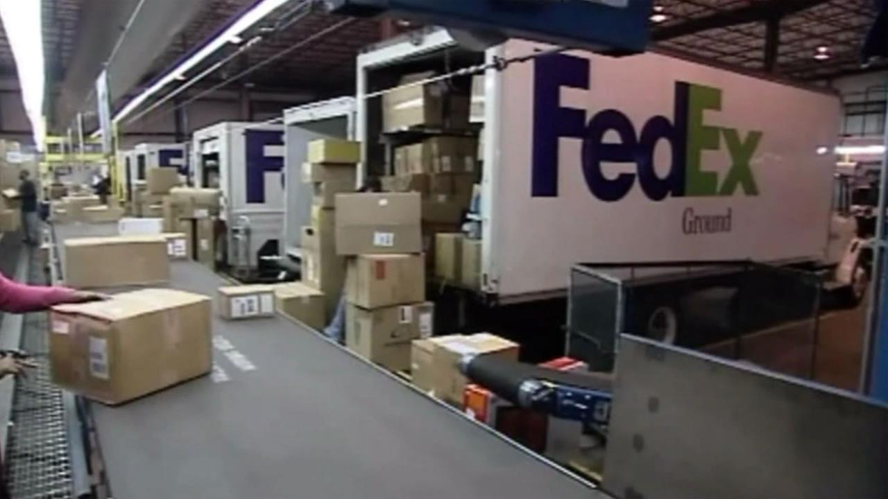 Packages are placed on a conveyor belt at a FedEx facility.