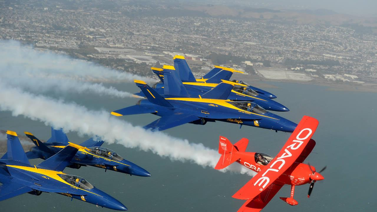 In preparation for Fleet Week performances, the U.S. Navy Blue Angels and Team Oracle stunt pilot Sean D. Tucker fly over the San Francisco Bay.