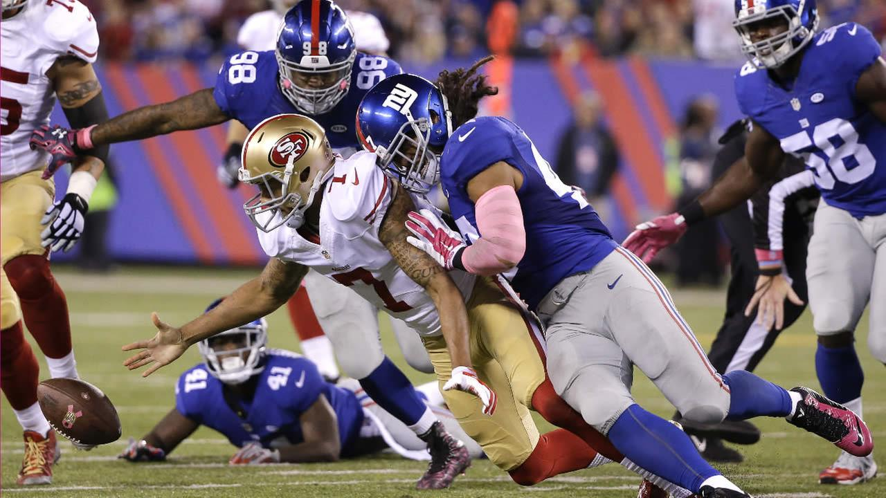 49ers Colin Kaepernick fumbles the ball as he is hit by Giants Uani Unga during the second quarter of an NFL football game on Oct. 11, 2015, in East Rutherford, N.J. (AP Photo)