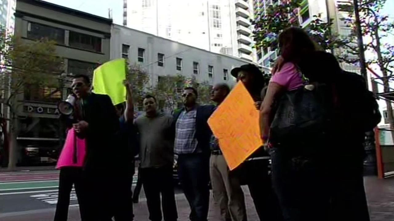 Uber drivers stood outside of the companys San Francisco headquarters Friday holding signs and protesting at the start of their 3-day work stoppage, Oct. 16, 2015.