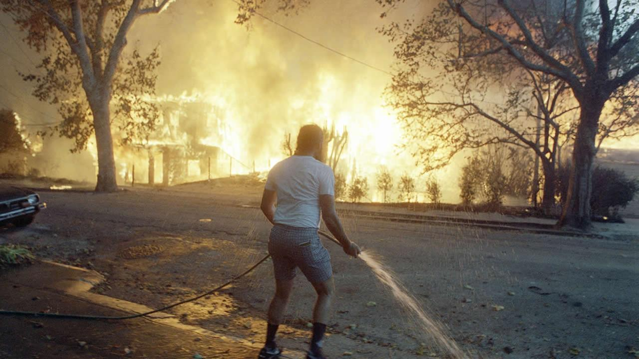 Berkeley resident Jim Beatty stands hopelessly with a garden hose as homes burn out of control in the Berkeley and Oakland hills area on Oct. 20, 1991 in Berkeley, California. (AP Photo/Kevin Rice)