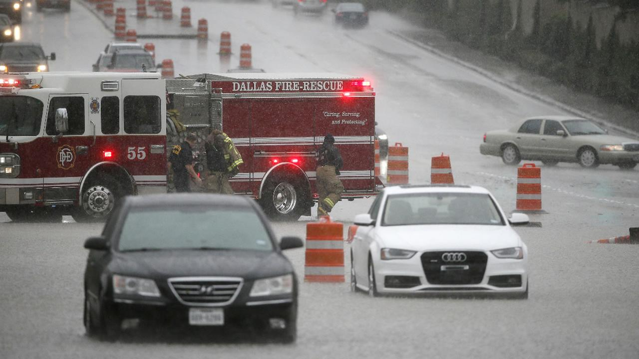 Dallas fire rescue responders close off a section of Hillcrest road after vehicles with drivers still inside stalled in the flood waters during a heavy rain fall Friday, Oct. 23, 2015, in Dallas.