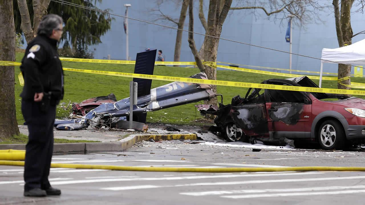 A police officer looks across at the wreckage of a news helicopter which crashed into a city street near the Space Needle Tuesday, March 18, 2014, in Seattle.