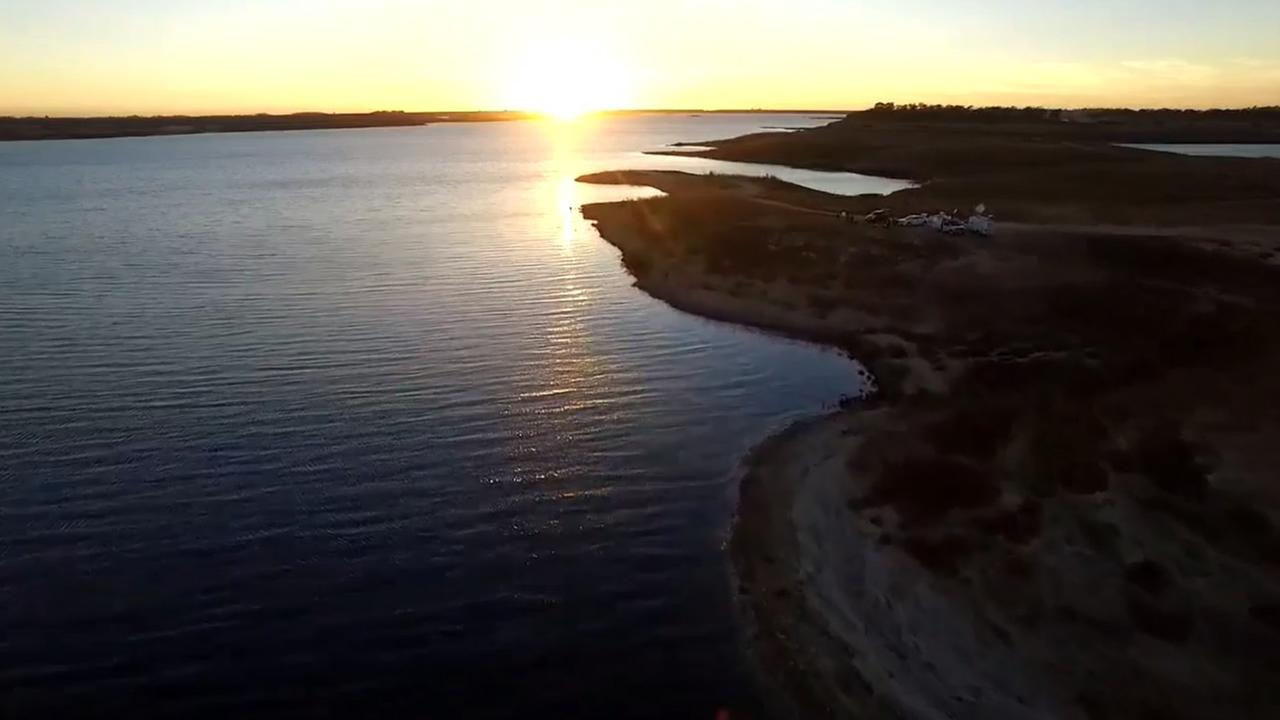 This image taken from DroneView7 shows the sunset over a parched Camanche Reservoir near Stockton, Calif. on Thursday, October 29, 2015.KGO-TV