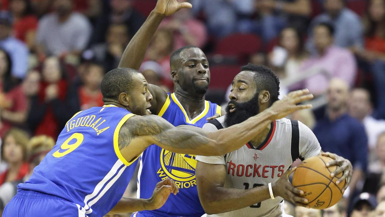 Houston Rockets James Harden, right, is double-teamed by Golden State Warriors Andre Iguodala, left, and Draymond Green, center, during a NBA basketball game Friday,Oct. 30, 2015.
