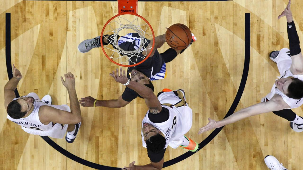 Golden State Warriors guard Stephen Curry goes to the basket between New Orleans Pelicans forward Ryan Anderson, forward Anthony Davis and center Omer Asik in a game in New Orleans, Saturday, Oct. 31, 2015.