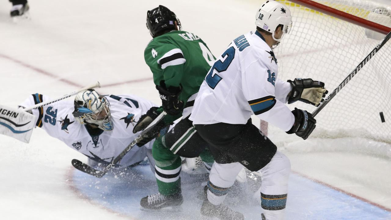Dallas Stars defenseman Jason Demers (4) scores a goal against San Jose Sharks goalie Alex Stalock (32) and center Patrick Marleau (12) during the second period of an NHL hockey game Saturday, Oct. 31, 2015, in Dallas.