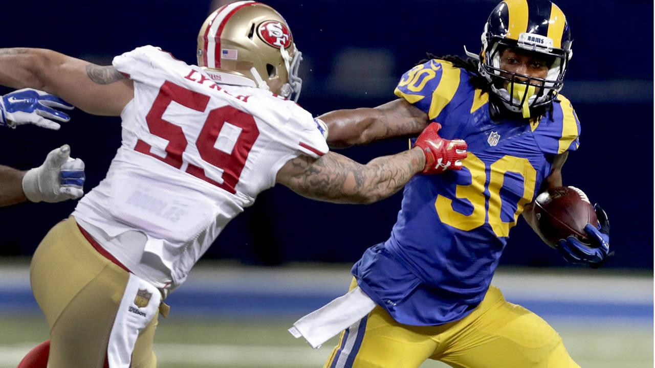 Rams Todd Gurley runs with the ball as 49ers Aaron Lynch defends during the third quarter of an NFL football game Sunday, Nov. 1, 2015, in St. Louis. (AP Photo/Tom Gannam)