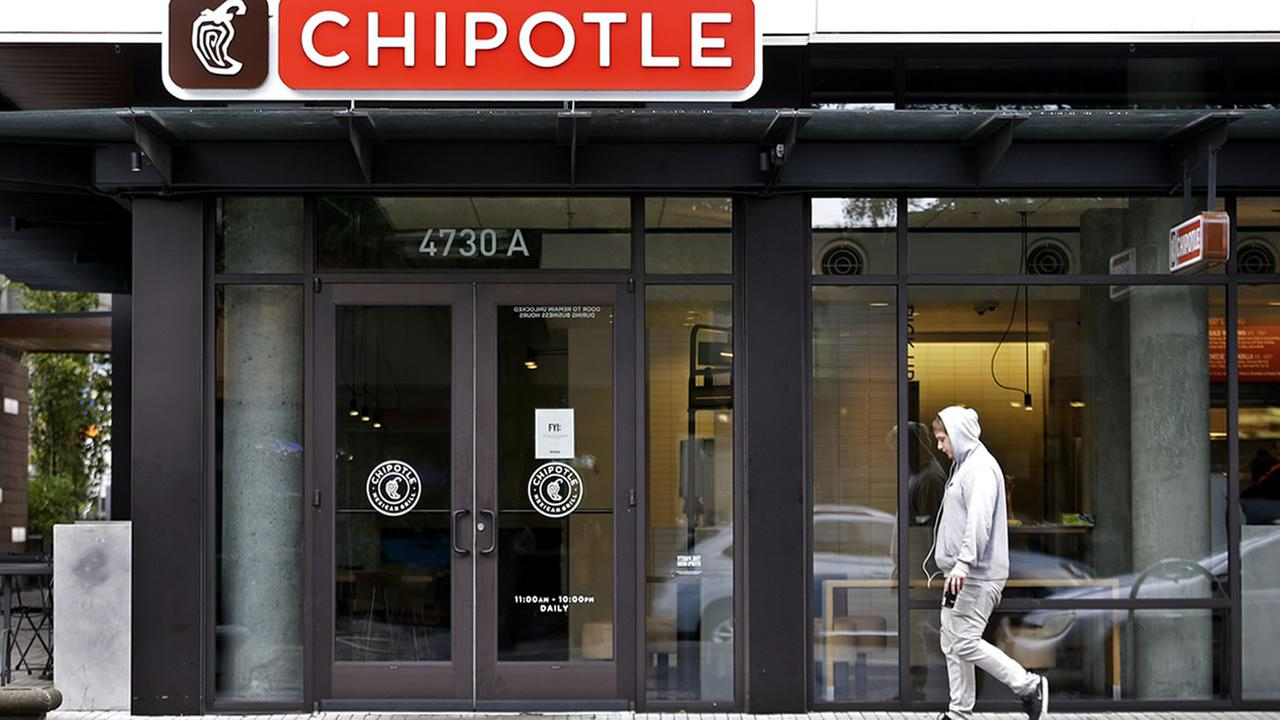 A pedestrian walks past a closed Chipotle restaurant Monday, Nov. 2, 2015, in Seattle. (AP Photo/Elaine Thompson)