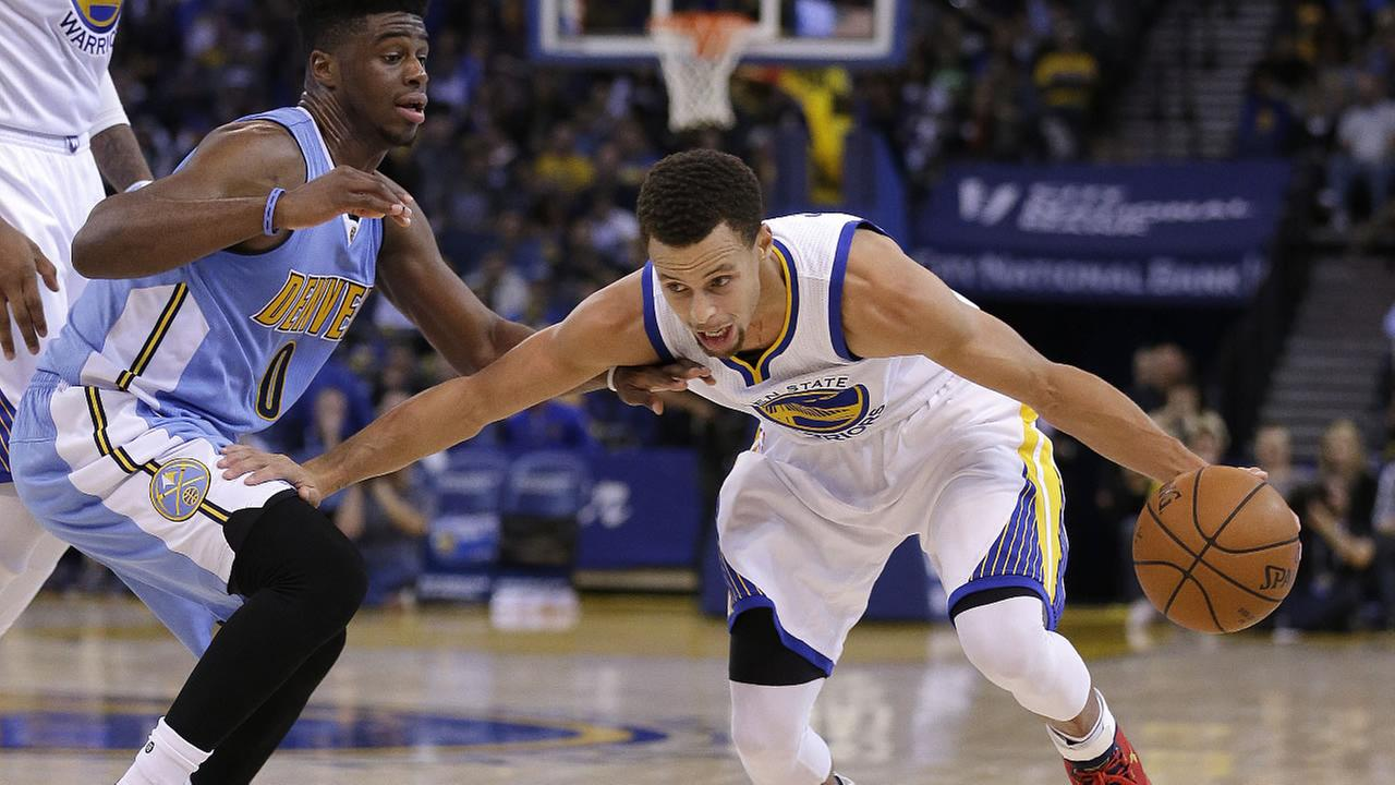Golden State Warriors Stephen Curry, right, drives the ball against Denver Nuggets Emmanuel Mudiay during the second half of an NBA basketball game Friday, Nov. 6, 2015.
