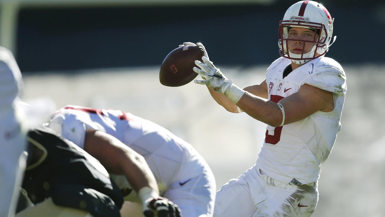 Stanford running back Christian McCaffrey, back, fades back to throw a pass for a touchdown against Colorado on Saturday, Nov. 7, 2015, in Boulder, Colo. Stanford won 42-10.