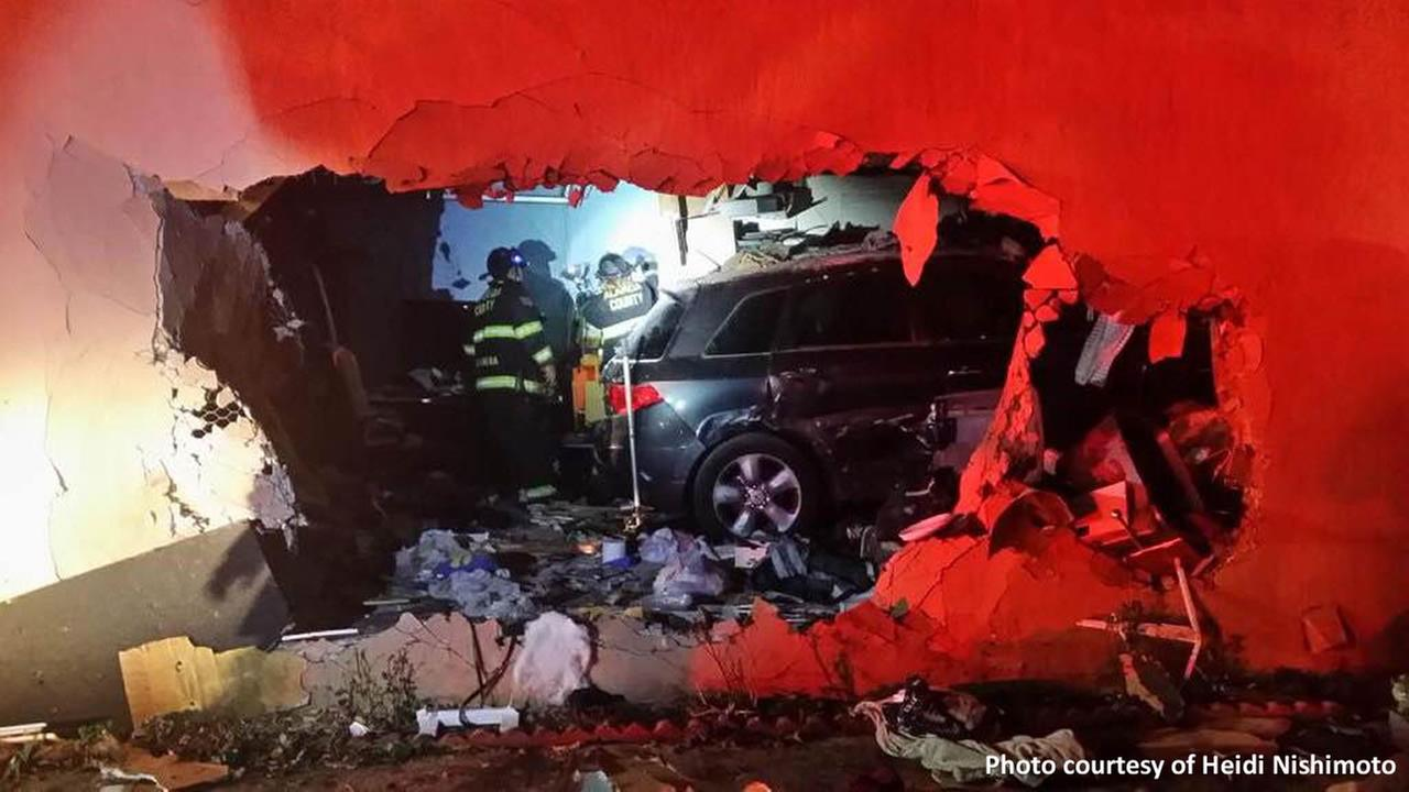 Firefighters respond to the scene of accident involving a car that drove into a home in San Leandro, Calif. Nov. 9, 2015.