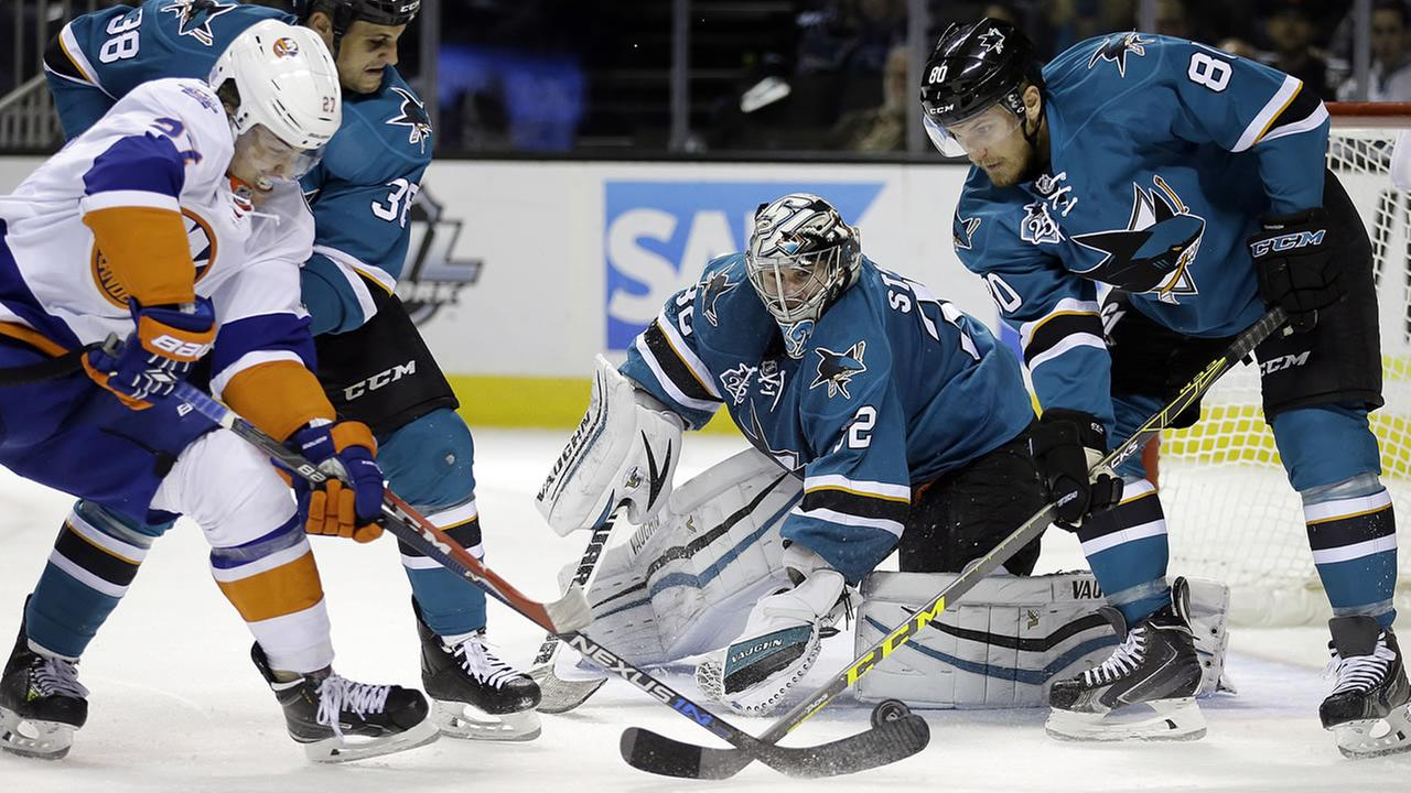 New York Islanders Anders Lee, left, takes a shot on goal against San Jose Sharks goalie Alex Stalock (32) during the second period of an NHL hockey game Tuesday, Nov. 10, 2015.