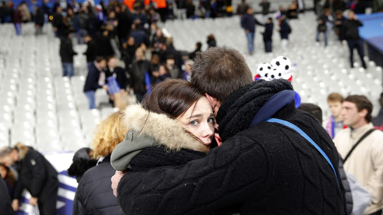 Spectators embrace each other as they stand on the playing field of the Stade de France stadium  in Saint Denis, outside Paris, Friday, Nov. 13, 2015.AP Photo/Christophe Ena